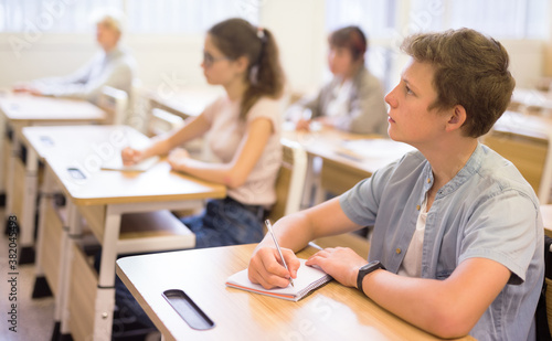 Foto Teen boy sitting at desk in classroom full of pupils during lesson