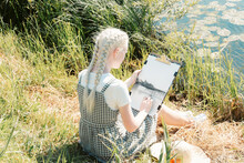 A Young Albino Woman In A Straw Hat, Sitting On The River Bank And Draws A Landscape On Canvas With Charcoal.