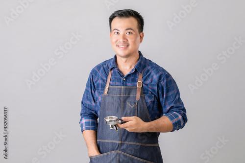 Valokuvatapetti Portrait Asian man in barista uniform holding Coffee Bottomless Portafilter in s