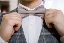 A Man Puts On A Bow Tie With H...