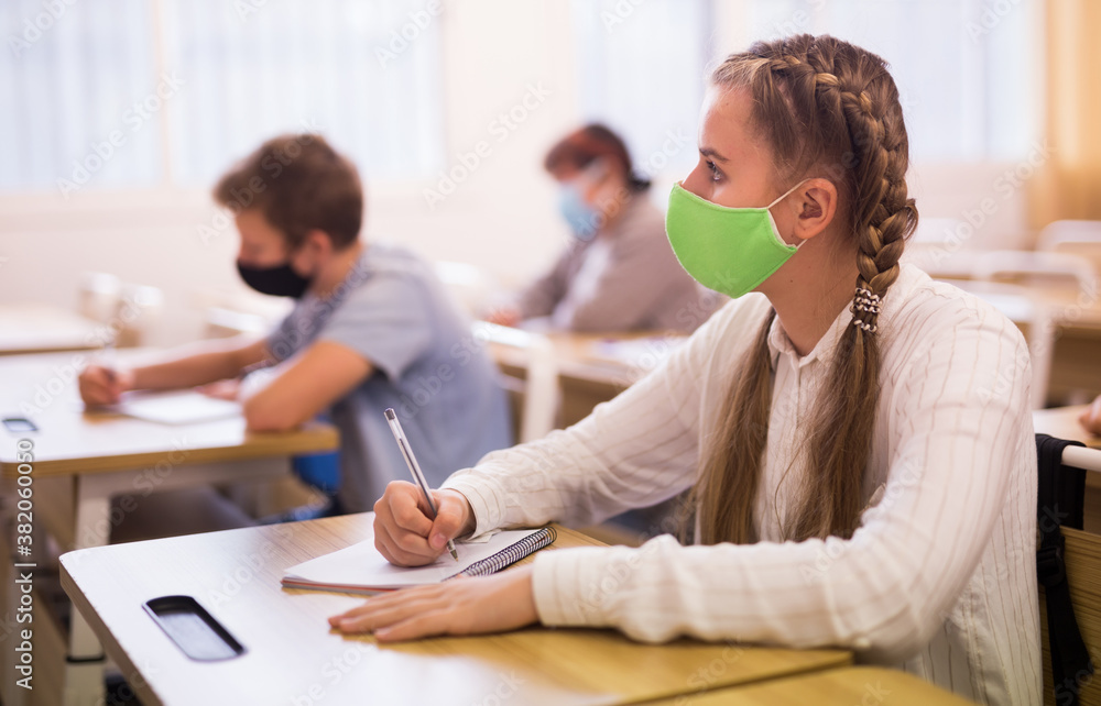 Fototapeta Portrait of diligent schoolgirl wearing protective face mask sitting in class working with classmates, new normal education during pandemic