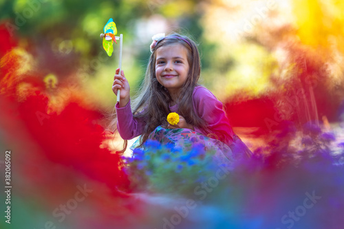 Fototapeta Happy young girl playing and blowing pinwheel in park with colorful flowers in slow motion obraz