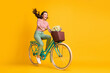 canvas print picture Full length body size photo of amazed girl shouting riding bicycle with basket of flowers isolated on vivid yellow color background