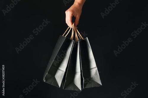 Female hand hold paper bags on black background Fotobehang
