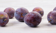 Ripe Plums On A Wooden White T...