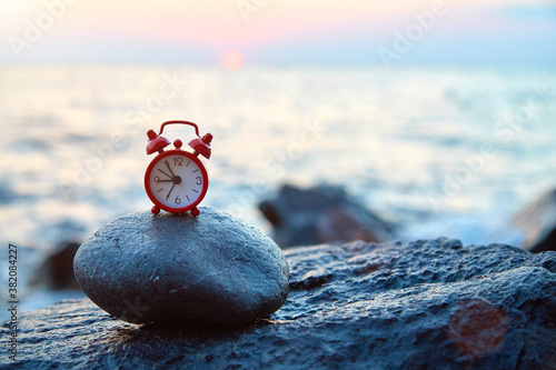 Fotografie, Obraz Red clock standing on round shaped stone