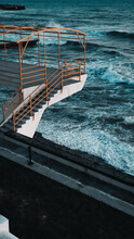 A White Pier With Yellow Railings Overhanging The Swirling Blue Sea. Big Foam Waves. Vertical Photo.