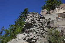 A Rocky Mountain Cliff With Tr...