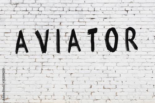 Fototapeta Inscription aviator painted on white brick wall