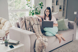 Photo portrait of relaxed woman sitting on sofa with laptop indoors