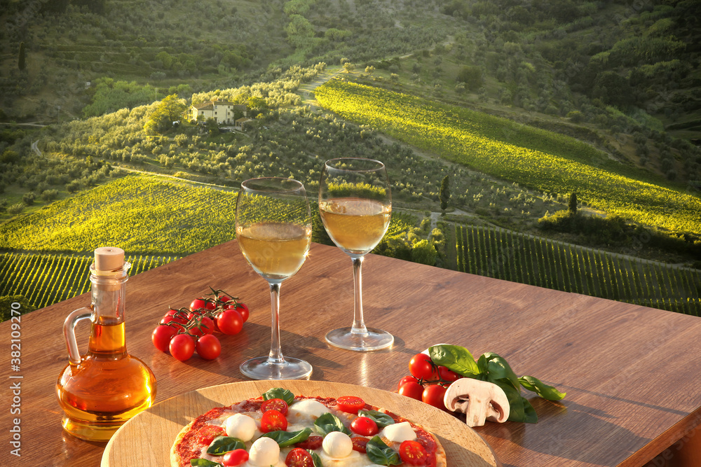 Italian pizza with glasses of white wine against Tuscan vineyards near the Florence in Italy