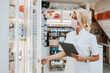 Young and attractive female pharmacist with face protective mask working in drugstore. She is confident and serious. Covid-19 open for business concept.