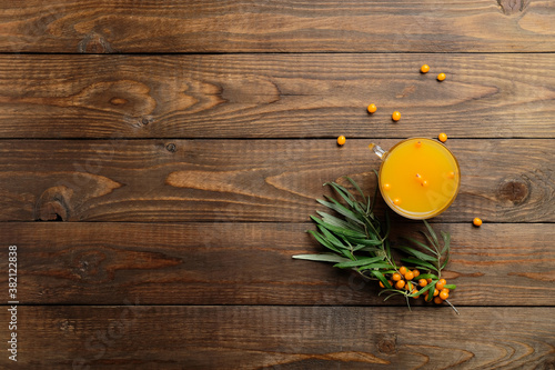 Fototapeta Sea buckthorn juice and plant branches with berries on wooden desk. Flat lay, top view, copy space. obraz