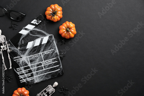 Cuadros en Lienzo Movie clapperboard and halloween decoration on black table