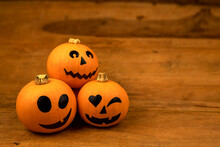 Little Pumpkins With Painted Faces For Halloween On Wooden Background