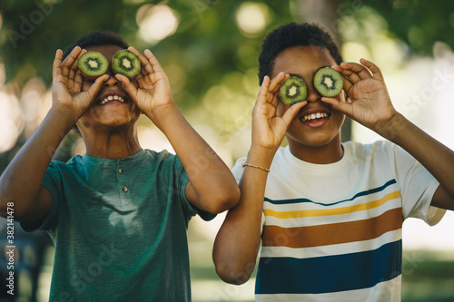 Fototapeta Two african cheerful boys standing outdoors and playing with kiwi fruit. obraz