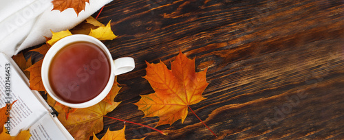 Fototapeta cup of coffee or tea with golden autumn leaves, plaid and book on a wooden background