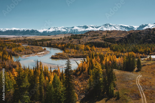 Fotografía Colourful mountain valley, blue snow covered peaks, orange and green autumn forest and river