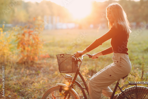Happy active young woman riding vintage bicycle with basket in autumn park at su Slika na platnu