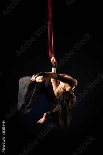 Photo Brunette beautiful caucasian woman in Lace mask doing circus tricks on red silks isolated on black background