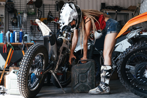 Female wearing shorts, motorcycle boots and cross-country helmet pouring gasoline into enduro motorcycle in the garage