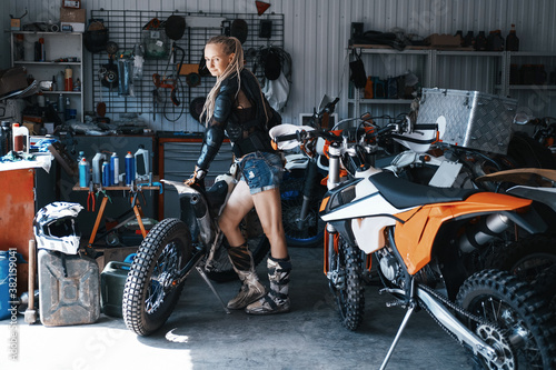 Female wearing shorts, moto boots and motorcycle .armor resting in garage with enduro motorcycles
