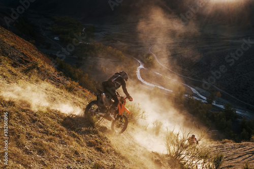 Fototapeta Extreme Rider climbing sand mountain top on off-road cross enduro motorcycle. Beautiful mountains landscape down on background, colourful autumn forest and river in sunshine obraz