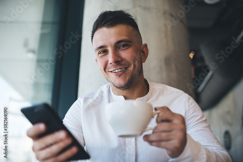 Smiling man using smartphone in cafe Canvas Print