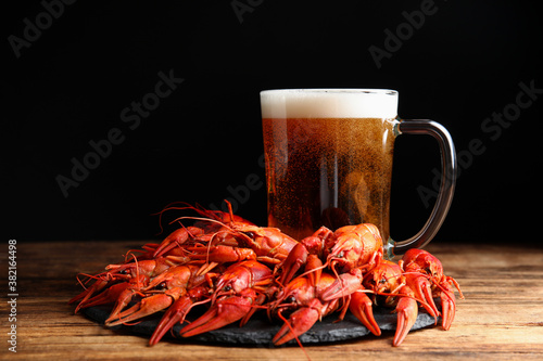 Delicious red boiled crayfishes and mug of beer on wooden table