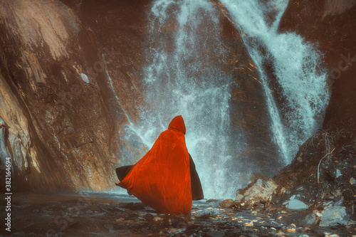 Photo Red cloaked figure in front of a mighty waterfall