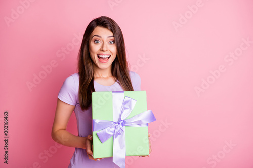 Photo of astonished young woman hold gift open mouth dressed casual purple outfit isolated on pink color background