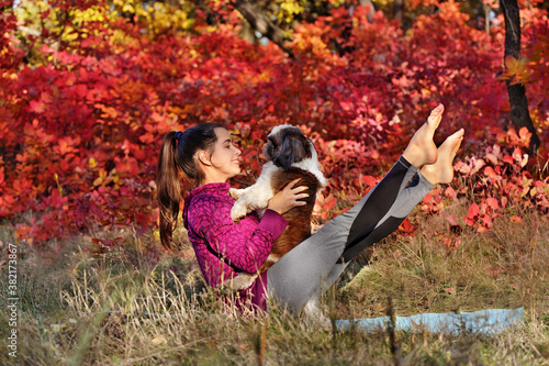 Fotografia Sporty woman practicing boat yoga pose with her dog