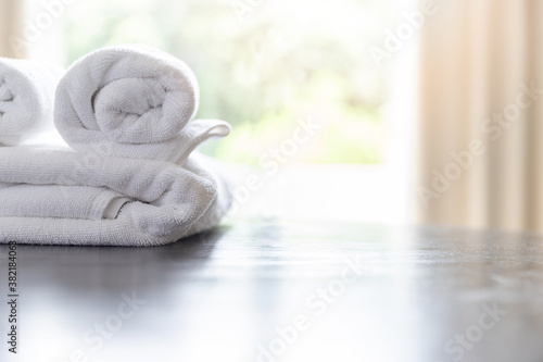 Fotografiet Roll up of white towels on table with copy space on blurred room background