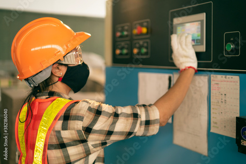 Cuadros en Lienzo Professional Industrial worker operate screen panel of heavy machine to setting a mechanic controller in factory atmosphere, Technician female engineer with safety wear and face mask in heavy factory