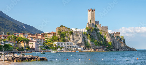 Fototapeta Malcesine - The beach of Lago di Garda lake with the town and castle in the background