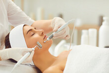 Woman Receiving Apparatus Facial Microcurrent Treatment From Therapist In Beauty Salon