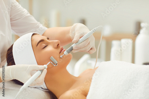 Fotografie, Obraz Woman receiving apparatus facial microcurrent treatment from therapist in beauty