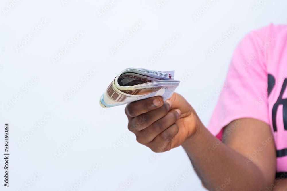 Fototapeta african woman stretches some money forward