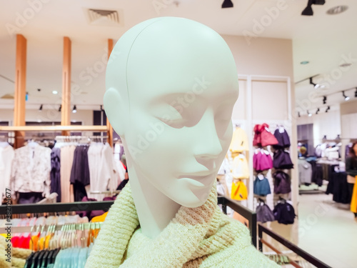 Fotomural Head of a white female mannequin without hair with downcast eyes on the backgrou