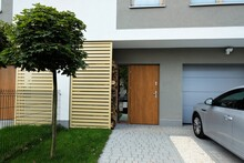 Entrance To A Modern Terraced House With Green Lawn, Maple Tree And Car Parked Outside