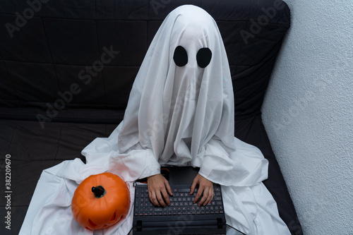 Valokuva Ghost working from home on his computer sitting on the couch with a pumpkin
