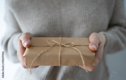 Fotografia Female hands holding a beautiful gift craft box on white background