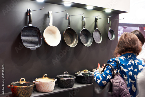 Valokuva Woman chooses pans in store household goods