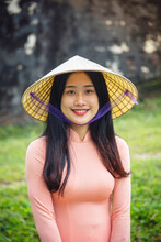 A Young Vietnamese Woman In A Traditional Ao Dai Dress And Conical Hat And Smiling, Hue, Vietnam