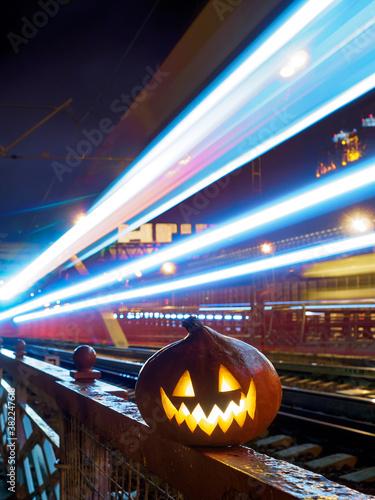 Halloween pumpkin with a glowing grimace at night on the railway bridge Fotobehang