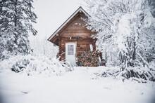 A Cozy Log Cabin In The Snowy Winter Landscape