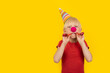 Boy with party hat and red clown nose holding whistle. Portrait on yellow background. Holiday matinee