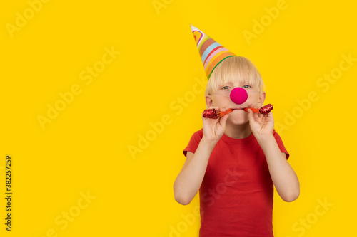 Boy with party hat and red clown nose holding whistle Fototapeta