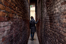 Man Walking In A Small Alley D...