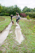 Little Girl Leaping Into A Huge Muddy Puddle